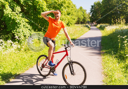 happy young man riding bicycle outdoors stock photo, fitness, sport, people and healthy lifestyle concept - happy young man riding bicycle outdoors by Syda Productions