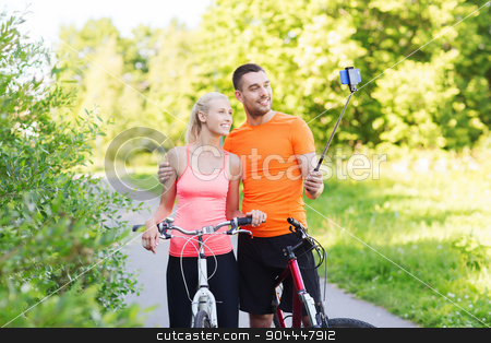 couple with bicycle and smartphone selfie stick stock photo, fitness, sport, people, technology and healthy lifestyle concept - happy couple with bicycle taking picture by smartphone on selfie stick outdoors by Syda Productions