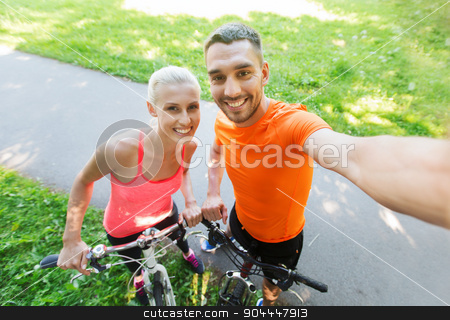 couple with bicycle taking selfie outdoors stock photo, fitness, sport, people, technology and healthy lifestyle concept - happy couple with bicycle taking selfie outdoors by Syda Productions