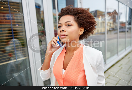african businesswoman calling on smartphone stock photo, business, communication, technology and people concept - young african american businesswoman calling on smartphone in city by Syda Productions