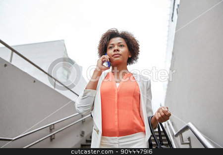 african businesswoman calling on smartphone stock photo, business, communication, technology and people concept - young african american businesswoman calling on smartphone going down stairs into city underpass by Syda Productions