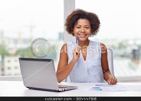 happy african woman with laptop at office stock photo, education, business and technology concept - happy african american businesswoman or student with laptop computer and papers at office by Syda Productions