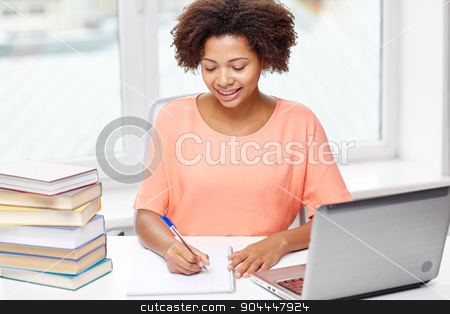 happy african american woman with laptop at home stock photo, people, technology and education concept - happy african american young woman sitting at table with laptop computer and books at home by Syda Productions
