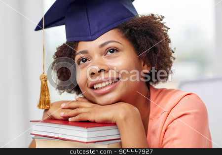 happy african bachelor girl with books at home stock photo, education, school, knowledge, graduation and people concept - happy smiling african american student girl in bachelor cap with books sitting at table and dreaming at home by Syda Productions