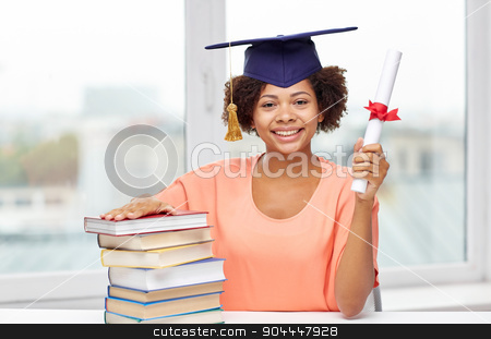 happy african bachelor girl with books and diploma stock photo, education, school, knowledge, graduation and people concept - happy smiling african american student girl in bachelor cap with books and diploma sitting at table at home by Syda Productions