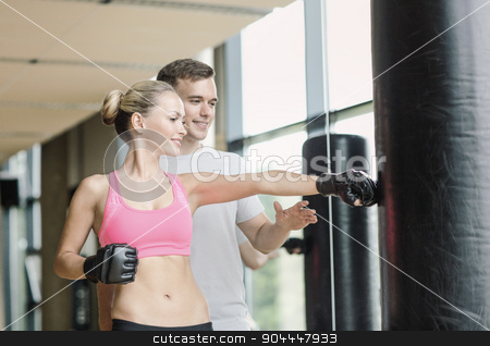 smiling woman with personal trainer boxing in gym stock photo, sport, fitness, lifestyle and people concept - smiling woman with personal trainer boxing in gym by Syda Productions