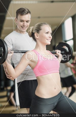 smiling man and woman with barbell in gym stock photo, sport, fitness, lifestyle and people concept - smiling man and woman with barbell exercising in gym by Syda Productions