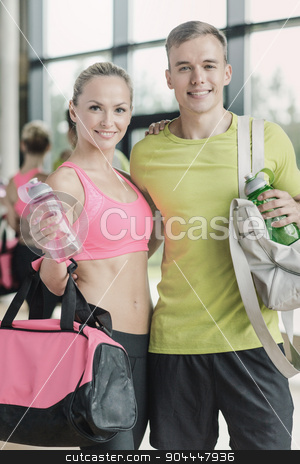 smiling couple with water bottles in gym stock photo, sport, fitness, lifestyle and people concept - smiling couple with water bottles in gym by Syda Productions