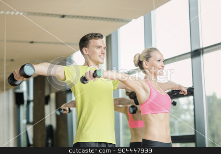 smiling man and woman with dumbbells in gym stock photo, sport, fitness, lifestyle and people concept - smiling man and woman with dumbbells exercising in gym by Syda Productions