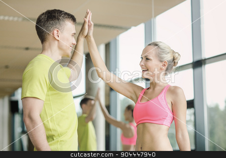 smiling man and woman making high five in gym stock photo, sport, fitness, lifestyle and people concept - smiling man and woman making high five in gym by Syda Productions