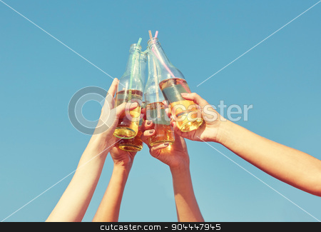 close up of many hands clinking bottles stock photo, summer vacation, holidays, party and people concept - close up of many hands clinking bottles with lemonade or beer over blue sky background by Syda Productions