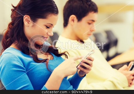 group of smiling students in lecture hall stock photo, education, high school, teamwork and people concept - group of smiling students with smartphones in lecture hall by Syda Productions