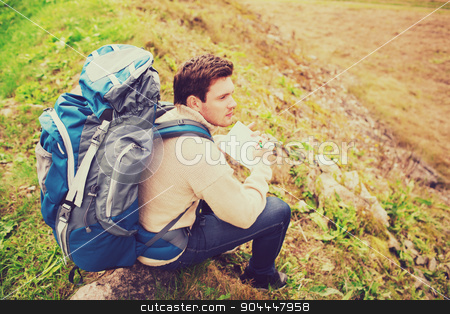 man with backpack hiking stock photo, adventure, travel, tourism, hike and people concept - man with backpack sitting on ground from back by Syda Productions