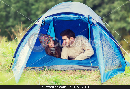 smiling couple of tourists looking out from tent stock photo, camping, travel, tourism, hike and people concept - smiling couple of tourists talking in tent by Syda Productions