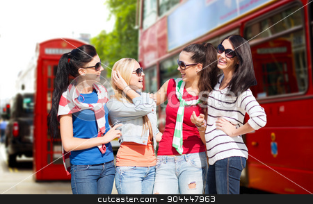 happy teenage girls or young women in london city stock photo, summer, holidays, vacation, friendship and people concept - happy teenage girls or young women in sunglasses talking and laughing over london city street background by Syda Productions