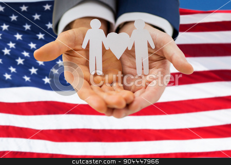 close up of happy male gay couple with love symbol stock photo, people, homosexuality, same-sex marriage and love concept - close up of happy male gay couple holding paper cutout love symbol over american flag background by Syda Productions