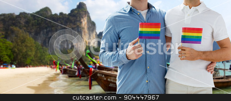 close up of male gay couple with rainbow flags stock photo, people, homosexuality, same-sex marriage, travel and love concept - close up of happy male gay couple holding rainbow flags and hugging over thailand beach background by Syda Productions