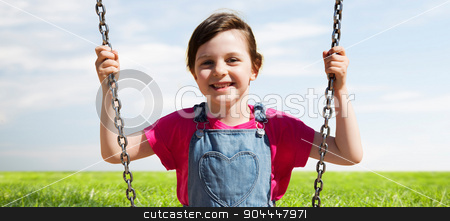 happy little girl swinging on swing outdoors stock photo, summer, childhood, leisure, friendship and people concept - happy little girl swinging on swing over blue sky and grass background by Syda Productions