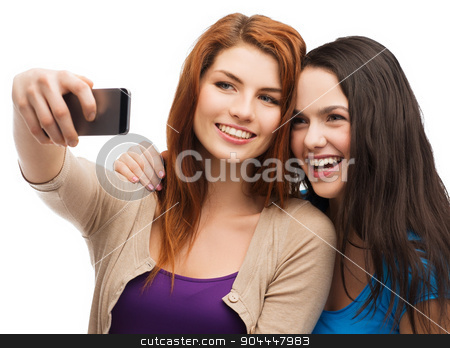 two smiling teenagers with smartphone stock photo, technology, friendship and people concept - two smiling teenagers taking picture with smartphone camera by Syda Productions