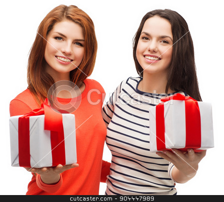 two smiling teenage girls with presents stock photo, holiday and happiness concept - two smiling teenage girls with presents by Syda Productions