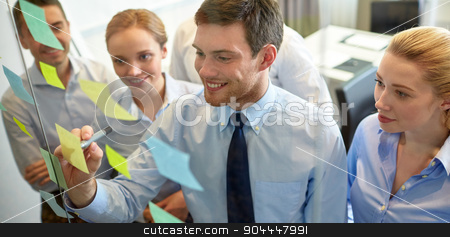 smiling business people with marker and stickers stock photo, business, people, teamwork and planning concept - smiling business team with marker and stickers working in office by Syda Productions