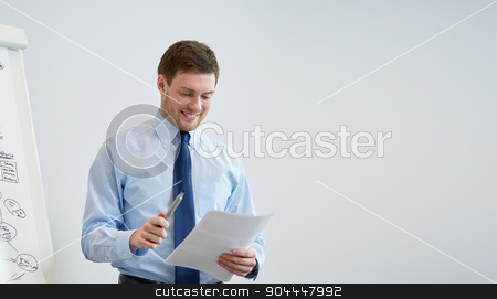 smiling businessman on presentation in office stock photo, business and people concept - smiling businessman on presentation in office by Syda Productions