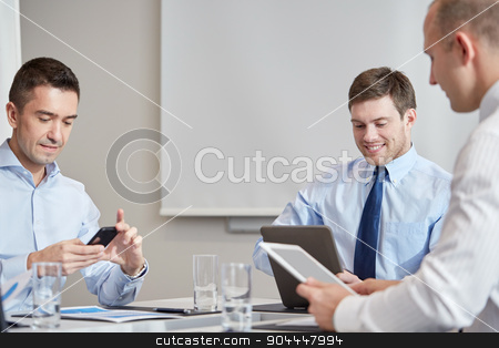businesspeople with smartphone and tablet pc stock photo, business, people, technology and teamwork concept - smiling businessmen with smartphone and tablet pc computers meeting in office by Syda Productions