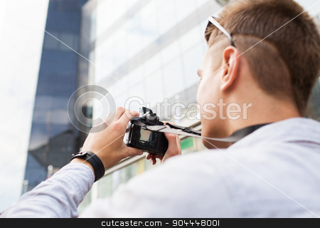 close up of young man with digital camera in city stock photo, people, photography, technology, leisure and lifestyle - close up of young man with digital camera taking picture on city street by Syda Productions