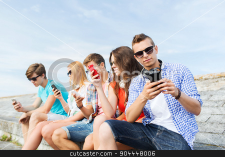 group of friends with smartphone outdoors stock photo, friendship, leisure, summer, technology and people concept - group of friends with smartphone outdoors by Syda Productions
