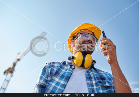 builder in hardhat with walkie talkie stock photo, industry, building, technology and people concept - male builder in hardhat with walkie talkie or radio outdoors by Syda Productions