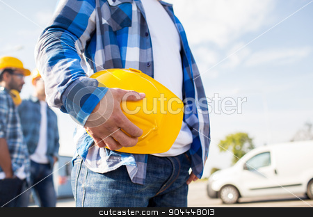 close up of builder holding hardhat at building stock photo, building, protective gear and people concept - close up of builder hand holding yellow hardhat or helmet at construction site by Syda Productions