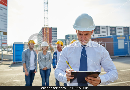 happy builders and architect at construction site stock photo, business, building, teamwork and people concept - group of smiling builders and architect with clipboard in hardhats at construction site by Syda Productions