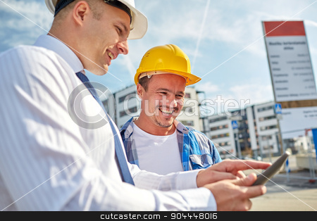 happy builders in hardhats with tablet pc outdoors stock photo, business, building, teamwork, technology and people concept - smiling builders in hardhats with tablet pc computer at construction by Syda Productions