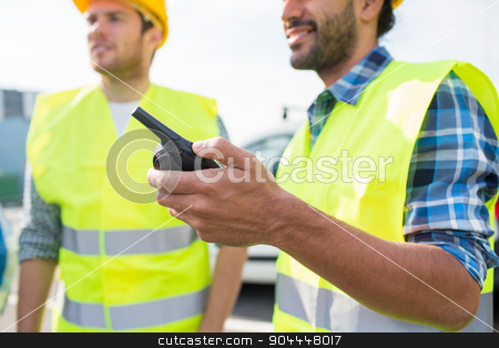 close up of builders in vests with walkie talkie stock photo, industry, building, technology and people concept - close up of male builders in high visible vests with walkie talkie or radio outdoors by Syda Productions