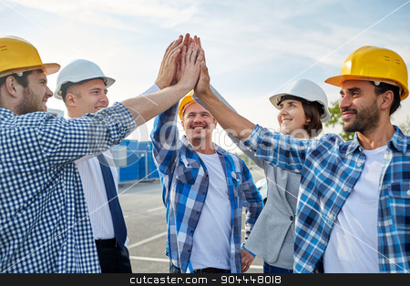 close up of builders in hardhats making high five stock photo, business, building, partnership, gesture and people concept - close up of smiling builders and architects in hardhats making high five outdoors by Syda Productions