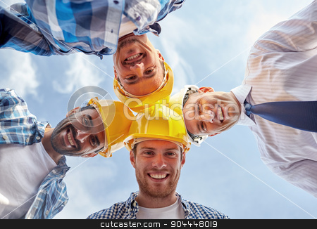 close up of builders wearing  hardhats in circle stock photo, business, building, partnership, construction and people concept - close up of smiling builders and architect in hardhats in circle outdoors by Syda Productions