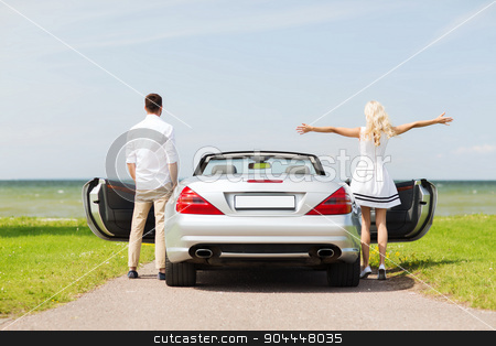 happy man and woman near cabriolet car at sea stock photo, transport, travel, road trip and people concept - happy man and woman near cabriolet car at sea side by Syda Productions