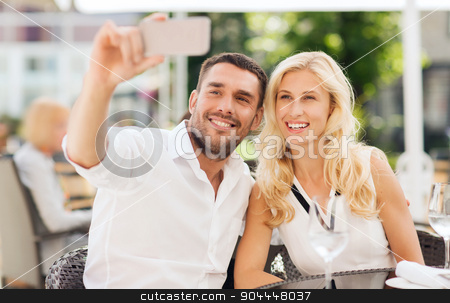 happy couple taking selfie with smatphone at cafe stock photo, love, date, technology, people and relations concept - smiling happy couple taking selfie with smatphone at city street cafe by Syda Productions