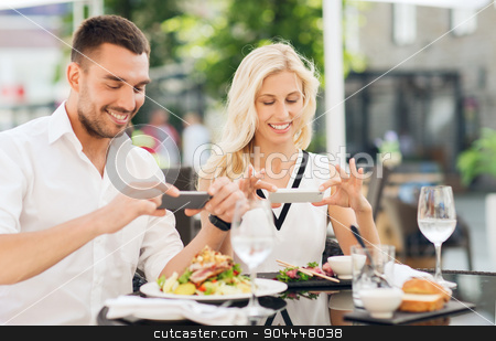 happy couple with smatphone photographing food stock photo, love, date, technology, people and relations concept - happy couple with smatphone taking picture of food at restaurant by Syda Productions