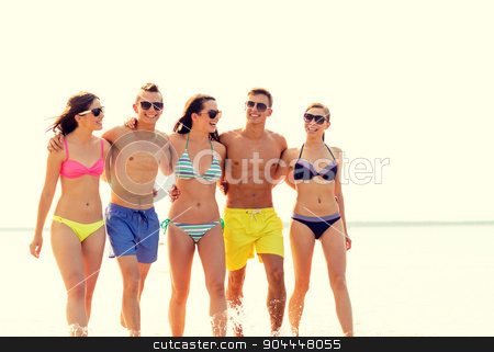 smiling friends in sunglasses on summer beach stock photo, friendship, sea, summer vacation, holidays and people concept - group of smiling friends wearing swimwear and sunglasses walking on beach by Syda Productions