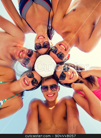 smiling friends in circle on summer beach stock photo, friendship, happiness, summer vacation, holidays and people concept - group of smiling friends wearing swimwear standing in circle with volleyball over blue sky by Syda Productions