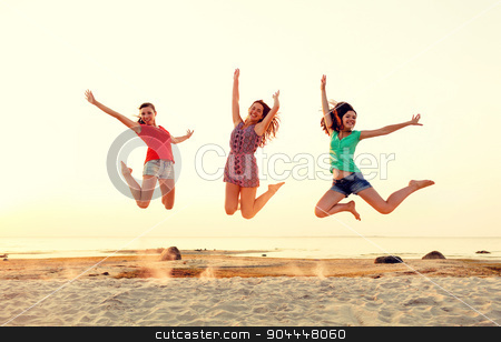 smiling teen girls jumping on beach stock photo, friendship, summer vacation, holidays, party and people concept - group of smiling teen girls jumping on beach by Syda Productions