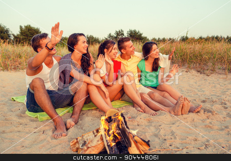 smiling friends in sunglasses on summer beach stock photo, friendship, summer vacation, holidays, gesture and people concept - group of smiling friends sitting near fire and waving hands on beach by Syda Productions