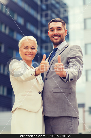 smiling businessmen showing thumbs up stock photo, business, partnership, success, gesture and people concept - smiling businessman and businesswoman showing thumbs up over office building by Syda Productions