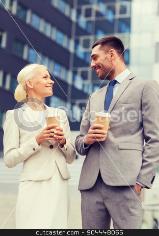 smiling businessmen with paper cups outdoors stock photo, business, partnership, hot drinks and people concept - smiling businessmen with paper cups standing over office building by Syda Productions