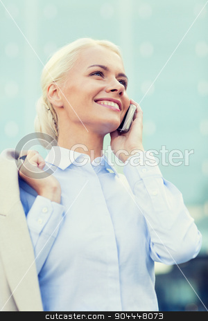 smiling businesswoman with smartphone outdoors stock photo, business, technology and people concept - smiling businesswoman with smartphone talking over office building by Syda Productions