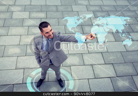 smiling businessman with world map projection stock photo, global business, development, technology and people and concept - young smiling businessman pointing finger to world map projection outdoors from top by Syda Productions