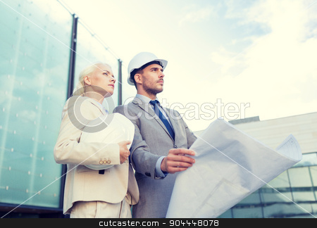 businessmen with blueprint and helmets stock photo, business, partnership, architecture and people concept - businessman and businesswoman with blueprint and helmets on city street by Syda Productions
