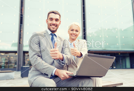 smiling businesspeople with laptop outdoors stock photo, business, education, technology, gesture and people concept - smiling businesspeople working with laptop computer showing thumbs up on city street by Syda Productions