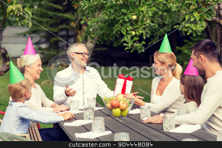 happy family having holiday dinner outdoors stock photo, family, happiness, generation, home and people concept - happy family with gift box having holiday dinner outdoors by Syda Productions